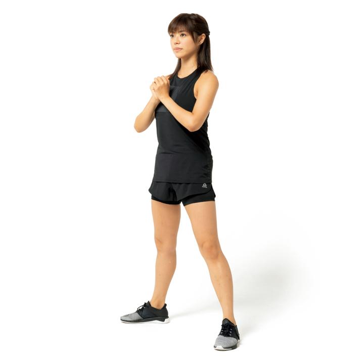 両足を肩幅より広く開いて立ち、胸の前で両手を組む。