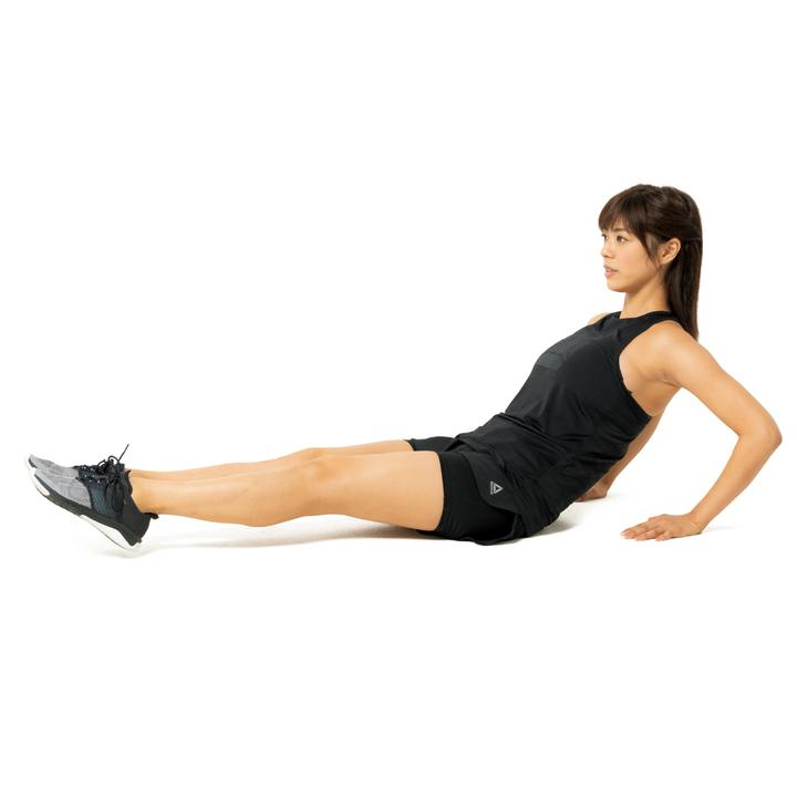 床に座って肩の少し横に両手をつき、肘を軽く曲げる。脚は揃えて伸ばし、床から数cm上げる。