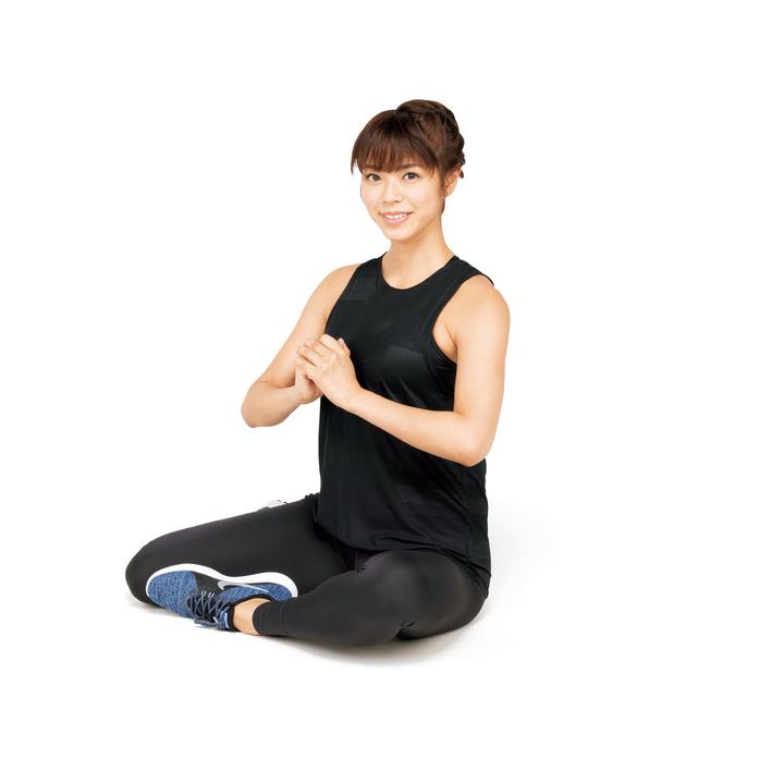あぐらをかき、片方の脚を股関節から後ろに回す。胸の前で手を組み、背すじを伸ばす。