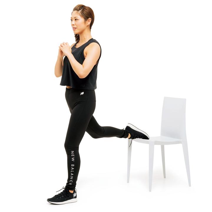 椅子の前に立ち、片方の足の甲を後ろの椅子の座面に置く。両手を胸の前で組む。