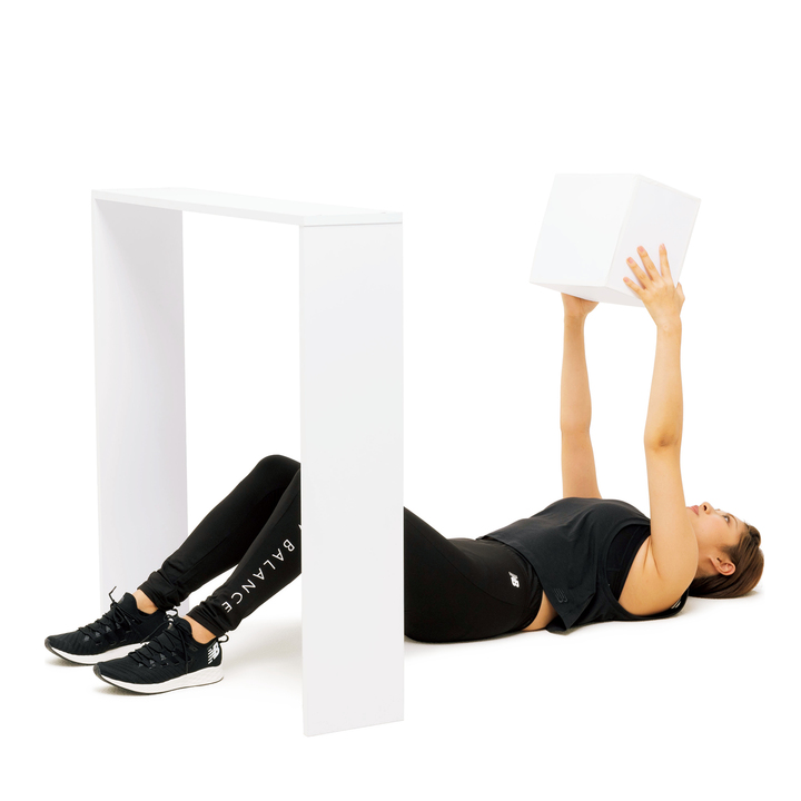 下半身が机の下に来るよう床に仰向けになり、膝を軽く曲げる。小さな段ボール箱を両手で持ち、肩の正面にまっすぐ上げる。