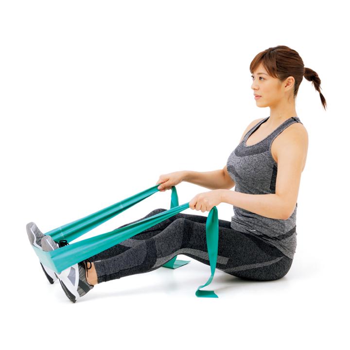脚を腰幅で伸ばして座り、足裏にチューブを通して両手で引く。チューブがピンと張るよう長さを調節し、膝を軽く曲げ、背すじを伸ばす。
