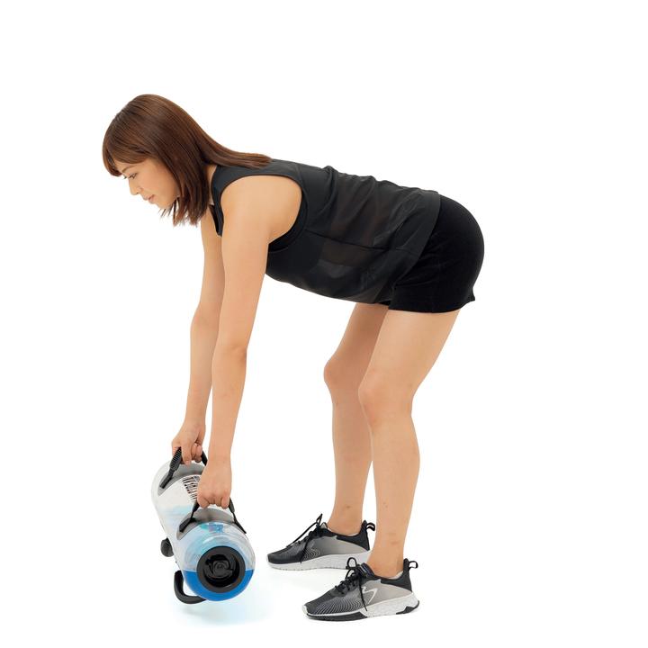 立位から腰を90度曲げて上体を前傾させ、肩の真下でバッグを持つ。
