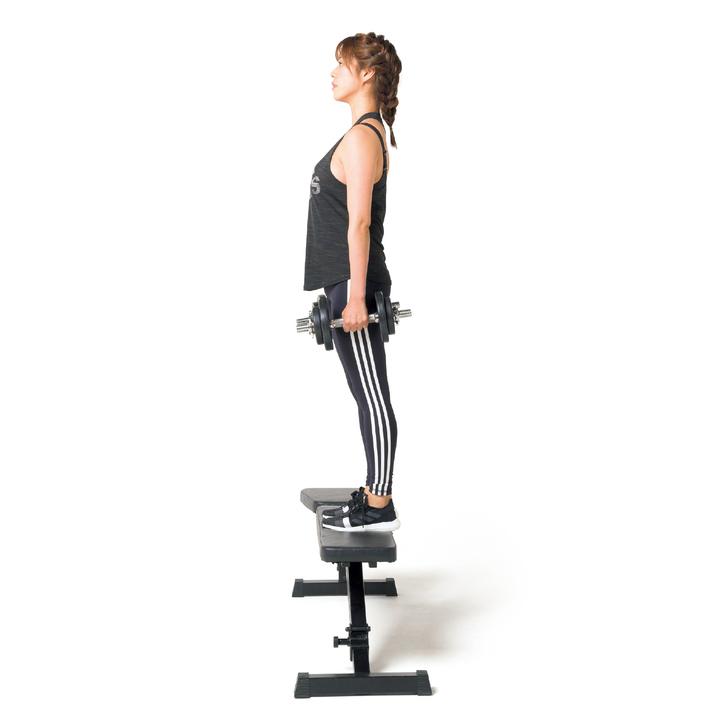 ベンチの前で、左右にダンベルを持ちまっすぐ立つ。姿勢を崩さずに片足をシートに乗せる。