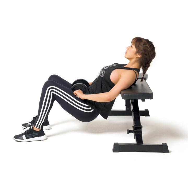 ベンチに直角に肩甲骨あたりをつけ、足を肩幅に開き、膝を曲げて尻を床から軽く浮かせる。ダンベルを両手で持ち、下腹部に置く。