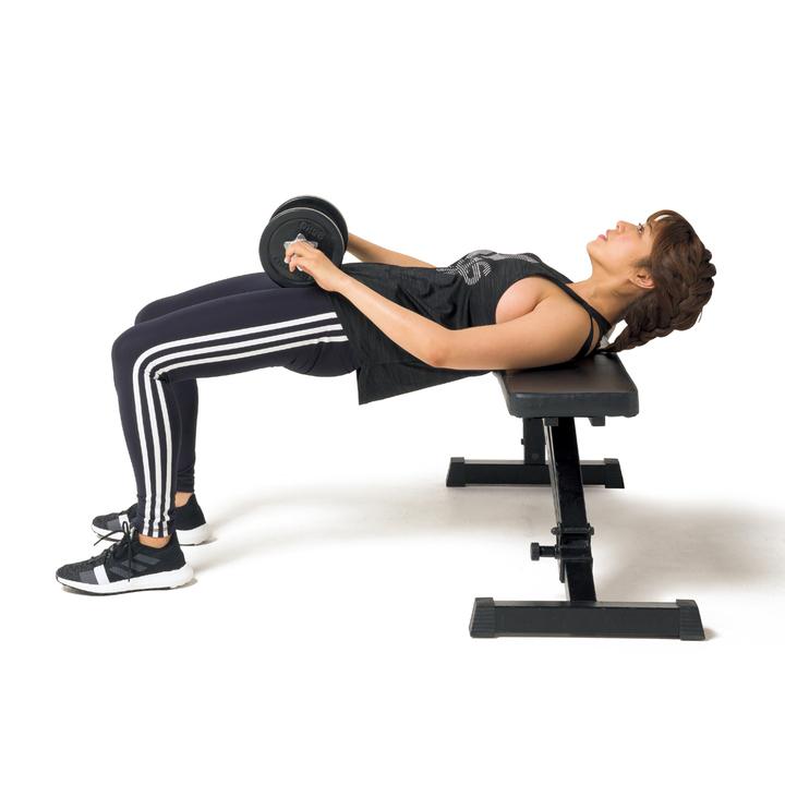 次に足裏で床を押しながらダンベルを押し上げるように腰を持ち上げる。上げ切ったところで少し静止し、元に戻す。10回行う。