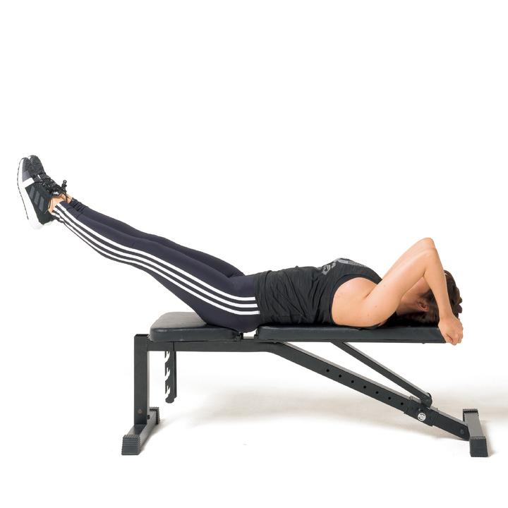 ベンチに仰向けになり、頭の横あたりのシートの端を両手で摑む。脚は揃えて伸ばし、床から浮かせる。