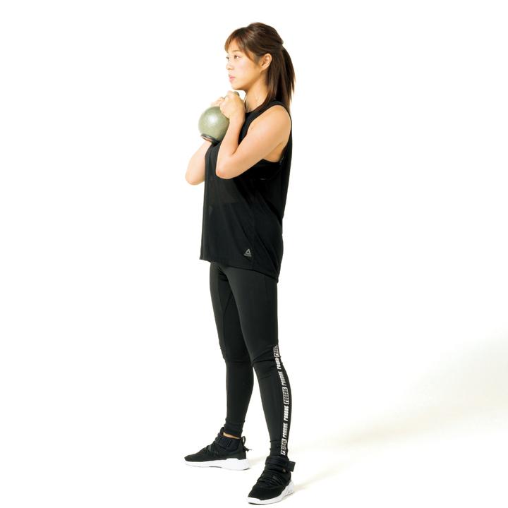 足幅を肩幅よりやや広げ、両手でケトルベルを持って直立。肘を曲げケトルベルを胸元に。