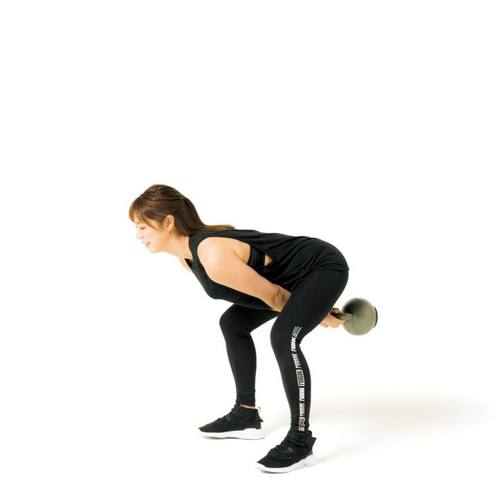 両手でケトルベルを持って足幅を肩幅より広げて立ち、お辞儀するように脚の付け根から曲げ、膝も軽く曲げる。ケトルベルは顔の真下へ。