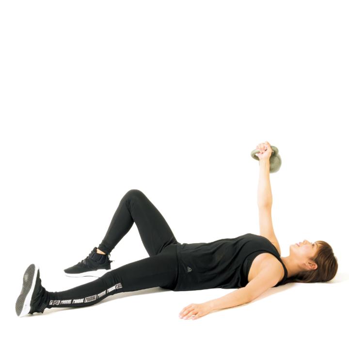 床に仰向けになり、右手で軽めのケトルベルを持ち床と垂直に上げる。