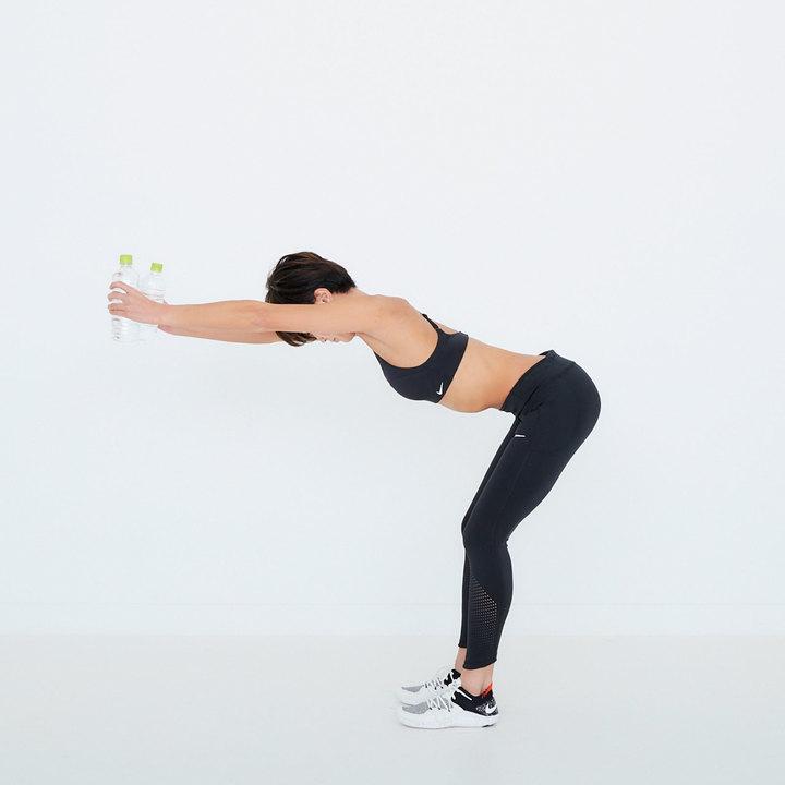 脚を腰幅に開いて立ち、両膝を軽く曲げる。胸を張ったまま股関節を曲げ、上体を前に倒す。ペットボトルを持った両手を頭の方向に伸ばす。