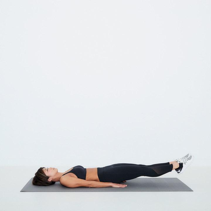両膝を伸ばして仰向けになる。両腕は体側に沿って自然に伸ばし、手のひらを床に。腰が浮かないよう注意しながら、両脚を床から少し浮かす。